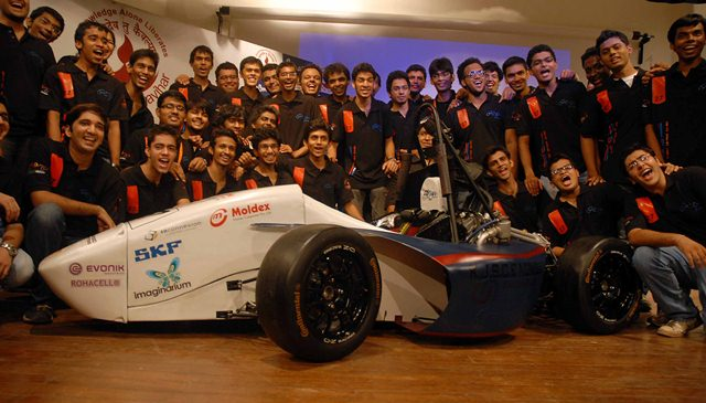 Engineering students during the launch of ORI 2012 a Formula type racing car